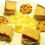 Turkey, lettuce and cheese sandwich with potato chips and chocolate chip cookies